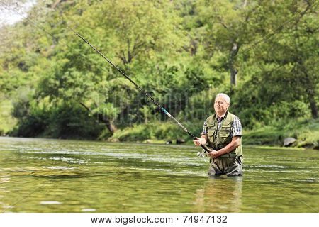Mature fisherman fishing in a river on a sunny day