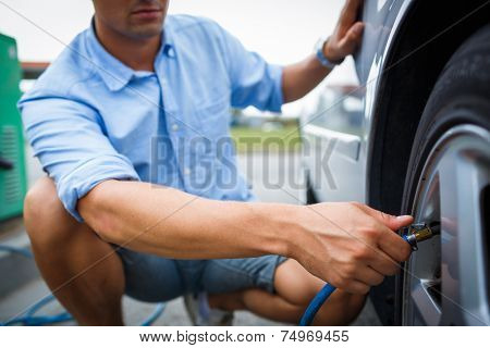 Driver checking air pressure and filling air in the tires of his modern car