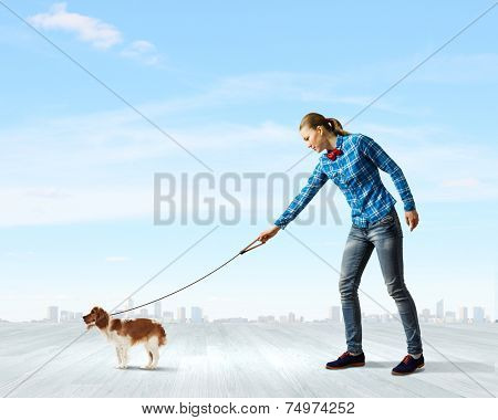 Young woman in casual holding dog on lead poster