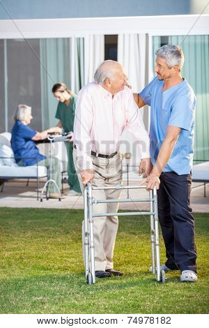 Male caretaker comforting senior man while assisting him in using Zimmer frame at nursing home lawn poster