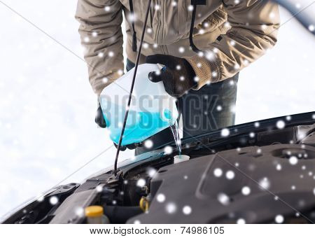 transportation, winter, people and vehicle concept - closeup of man pouring antifreeze into car