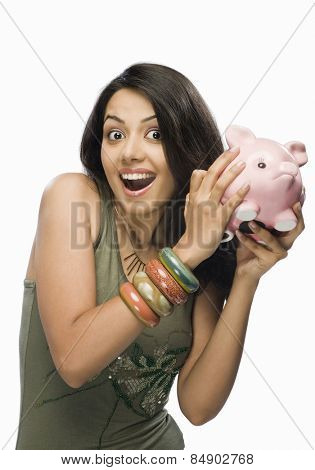 Portrait of a young woman shaking a piggy bank