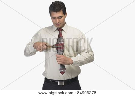 Businessman cutting his tie by scissors
