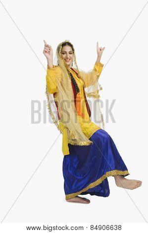 Woman in traditional yellow Punjabi dress doing bhangra