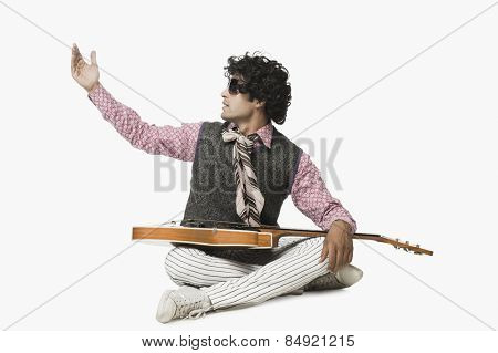 Businessman sitting with a guitar and singing