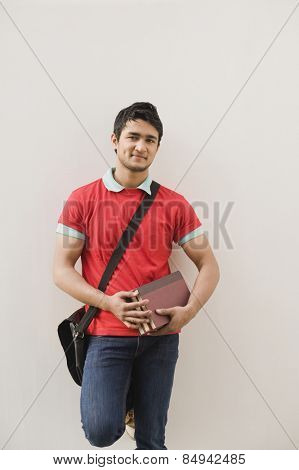 Man leaning against a wall and holding books