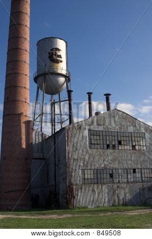 Abandoned Factory Building With Water Tower And Chimney