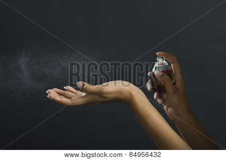 Woman applying perfume on her hand