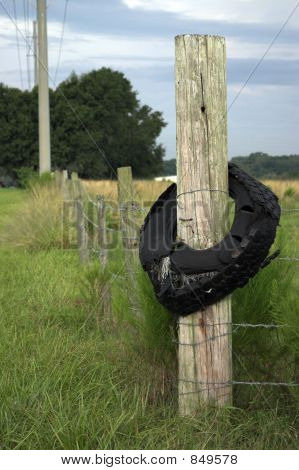 Old Tire On A Wooden Fence Post
