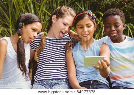 Portrait of happy children taking selfie at the park