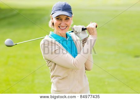 Female golfer taking a shot and smiling at camera on a sunny day at the golf cours