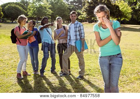 Student being bullied by a group of students on a sunny day