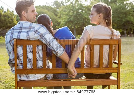 Man being unfaithful in the park on a sunny day