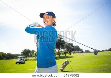 Lady golfer teeing off and smiling on a sunny day at the golf course