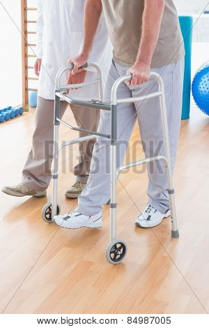 Senior man on zimmer frame with therapist in fitness studio