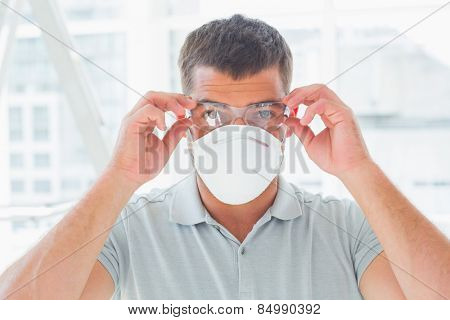 Portrait of confident handyman wearing protective eyewear and mask at site