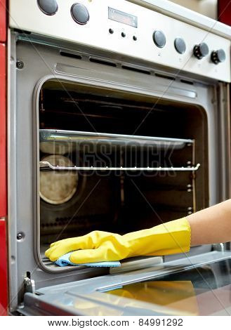 poster of people, housework and housekeeping concept - close up of woman hand in protective glove with rag cleaning oven at home kitchen