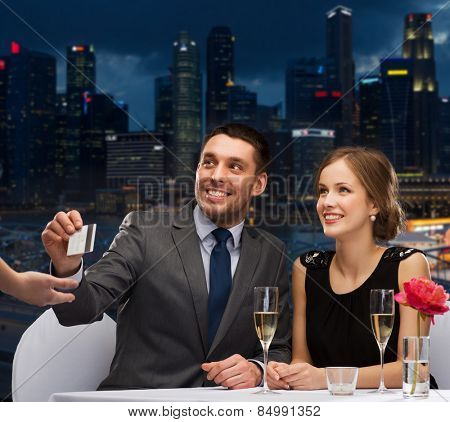 restaurant, people and holidays concept - smiling couple paying for dinner with credit card at restaurant over night city background