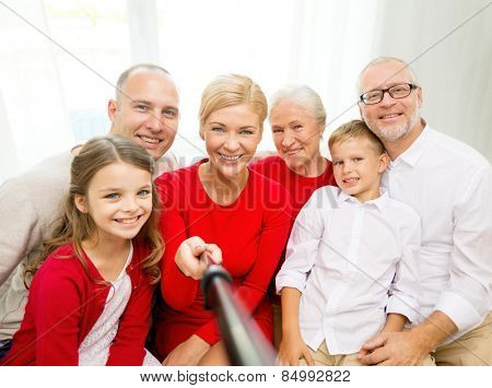 family, holidays, generation, christmas and people concept - smiling family with camera and stick making picture at home