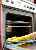 people, housework and housekeeping concept - close up of woman hand in protective glove with rag cleaning oven at home kitchen poster