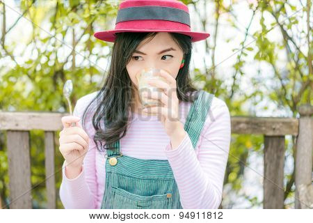 Beautiful Young  Asian Girl In Outdoor Cafe Drinking Coffee.