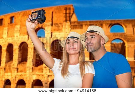 Beautiful couple taking picture of them self on Coliseum background, happy young family spending summer vacation in Rome, Italy, Europe