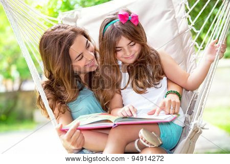 Portrait of beautiful mother with cute little daughter sitting on backyard in hammock and reading funny story, happy family life