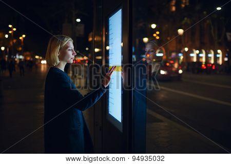 Charming woman verifies account balance on banking application via modern device icon