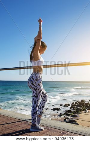 Woman stretching before her run while standing on wooden jetty with beautiful beach coastline