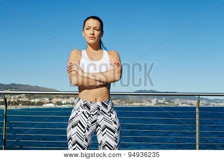 Healthy young woman in sports clothing with her arms crossed standing on sky background outdoors