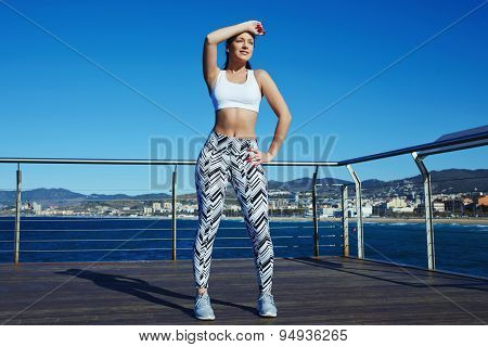 Charming female runner holding hand above her forehead while taking a break after fitness training