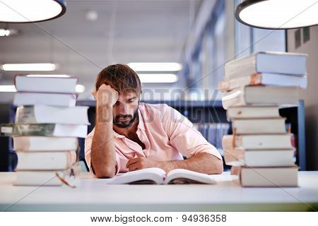 Frustrated male student sitting at the desk with a huge pile of study book in university library