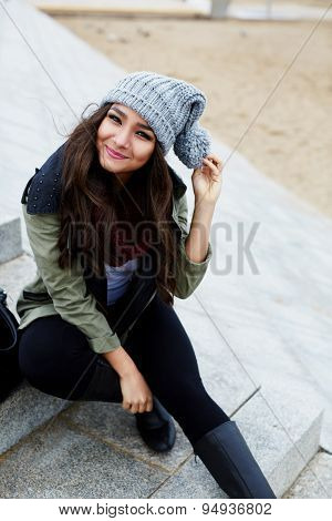 Portrait of smiling woman sitting on the steps at leisure time outdoors cold autumn day