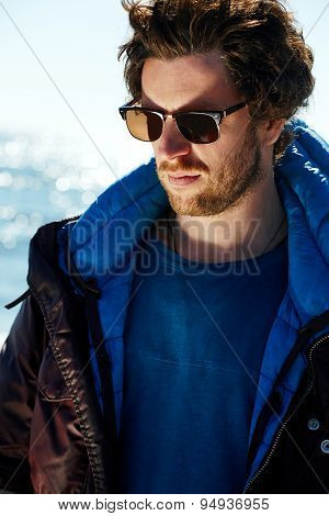 Young traveler man dressed in winter jacket and glasses standing on the beach at early morning
