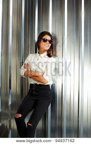 Portrait of smiling fashionable model standing on wall silver background in sunglases