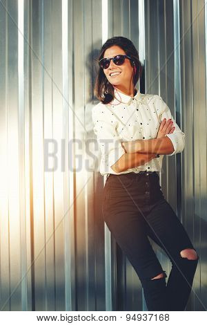 Portrait of attractive brunette hipster woman posing on shiny wall background in sunglases