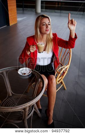 Charming female executive consumer asking for a bill at cafe during business lunch break