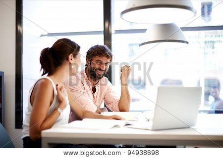 Little team of businesspeople smiling and looking together at computer discussing fun project