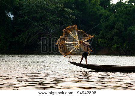 Fisherman is throwing fishing net in Hue, Vietnam