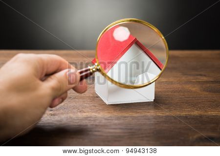 Person Hand With Magnifying Glass And Miniature House