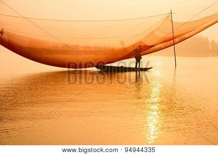 Unidentified fisher man check his nets in early morning on river in Hoian, Vietnam.