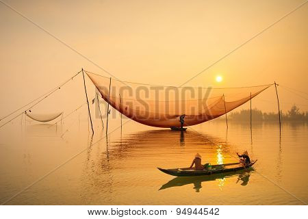 Two women on boat go to market in sunrise in a village of Cua Dai, Hoi An, Vietnam