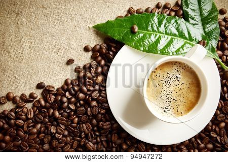 Coffee With Foam Cup With Beans In The Corner With Green Leaf On Flax