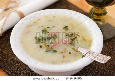 Caldo verde - soup in Portuguese brazilian cuisine in white plate. Selective focus poster