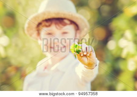 Lucky happy boy in hat holds four leaf clover