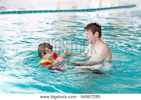 Little Kid Boy And His Father Swimming In An Indoor Pool