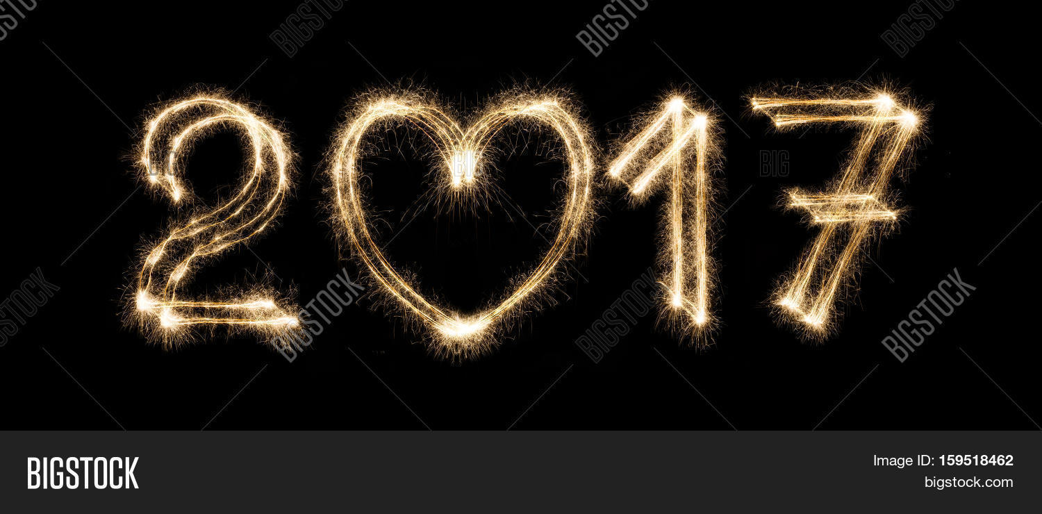 2017 new year text from sparkler firework on black background with heart shape love symbol