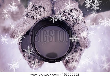 Hands in mittens with a cup close up on light background with snow and snowflakes. Woman hands in teal gloves holding a cozy mug with hot tea or coffee. Winter and Christmas time concept.