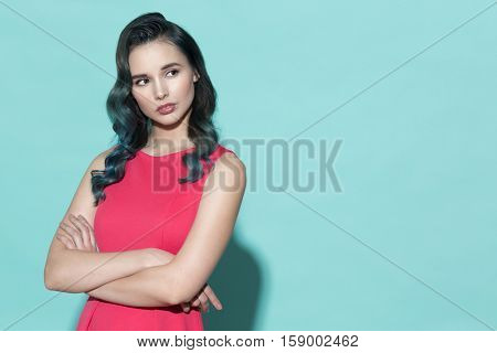 Fashion portrait of stylish woman in a pink dress. On a blue background.