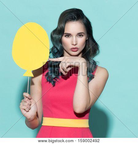 Beautiful stylish woman holding paper balloon. On a blue background.